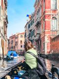 A young woman enjoys a gondola ride and making photo in the canals of Venice. royalty free stock photo