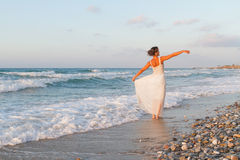 Young woman enjoys a lonesome walk on the beach at dusk. Stock Photography