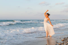 Young woman enjoys a lonesome walk on the beach at dusk. Royalty Free Stock Images
