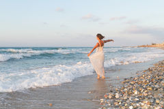 Young woman enjoys a lonesome walk on the beach at dusk. Royalty Free Stock Photos