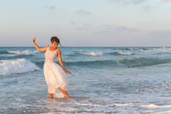 Young woman enjoys a lonesome walk on the beach at dusk. Royalty Free Stock Photo