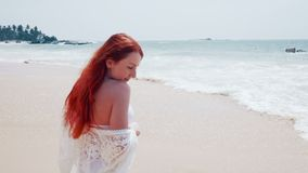 Young woman enjoys relaxing at the ocean. Young happy woman standing with hair flying on the wind on the ocean shore on a sunny day, slow motion stock video footage