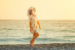 Young woman enjoys relaxing at the seaside. At sunset Royalty Free Stock Images