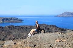 Young woman enjoys sea view sitting on a stone at volcano of San Stock Photos