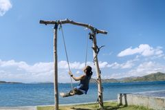 Young woman enjoys seascape on the swing royalty free stock images