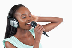 Young woman enjoys singing. Against a white background royalty free stock photos