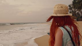Young woman enjoys a smartphone on a tropical beach. At sunset stock video footage