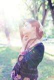 Young woman enjoys sun beams at spring park Royalty Free Stock Photo