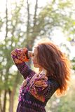 Young woman enjoys sun beams at spring park. Young woman with beautiful hair enjoys sun beams at spring park Royalty Free Stock Image