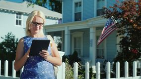 A young woman enjoys a tablet, stands near her American house with the American flag on it. 4k video stock video footage