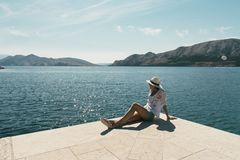 Young woman enjoys vacation. Baska harbour, Krk island. Beautiful view of islands. Summer vacations. Beautiful girl resting on bea. Ch. Straw hat royalty free stock image