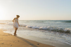 Young woman enjoys walking on a hazy beach at dusk. Stock Photography