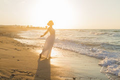 Young woman enjoys walking on a hazy beach at dusk. Royalty Free Stock Images