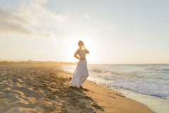 Young woman enjoys walking on a hazy beach at dusk. Royalty Free Stock Image