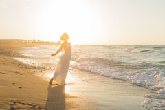 Young woman enjoys walking on a hazy beach at dusk. Royalty Free Stock Photography