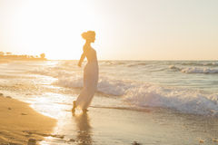 Young woman enjoys walking on a hazy beach at dusk. Royalty Free Stock Photo