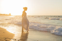 Young woman enjoys walking on a hazy beach at dusk. Barefoot young woman in a long white dress enjoys a lonesome walk on a sandy beach in a late summer hazy day Royalty Free Stock Photo