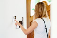 Young woman entering authorization code. Pin on home alarm keypad. Home security concept Stock Photo