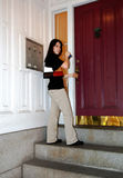 Young woman entering city apartment. A young woman unlocking the entrance to her city apartment stock image