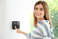 Young woman entering code on alarm system keypa. D indoors stock photo