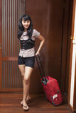 Young woman entering a hotel room. Beautiful asian woman entering a hotel room, shot at a 5 stars hotel room Royalty Free Stock Photo