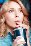 Young woman enthusiastically drinking coke in Royalty Free Stock Images