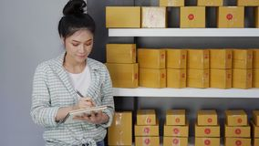 Young woman entrepreneur counting parcel boxes in her own job shopping online business. At home stock footage