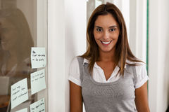 Young woman entrepreneur in her startup office. Smiling Royalty Free Stock Photo