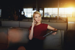 Young woman entrepreneur talking on mobile phone while waiting for her order in a restaurant during break, Stock Images