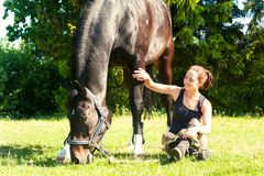 Young woman equestrian sitting close to her horse on grass. Young woman equestrian sitting close to her dark horse on green grass. Vibrant multicolored Stock Photography