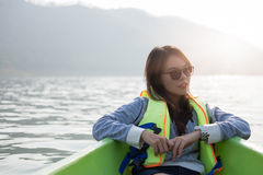 Young woman equip life jacket sitting relaxing on prow. she look Royalty Free Stock Images