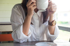 Young woman equip white shirt holding coffee cup and drinking co. Young woman equip white shirt holding coffee cup and drinking hot coffee in morning time. this Royalty Free Stock Photo