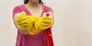 Young woman equipped with spray bottle and sponge. Housekeeping and cleaning concept. Women preparing to clean up bath. Young woman equipped with spray bottle stock photo