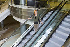 Young woman on escalator Royalty Free Stock Photo