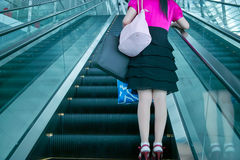 Young woman on escalator Stock Photo