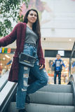 Young woman on escalator in mall Stock Photography
