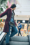 Young woman on escalator in mall Royalty Free Stock Photos