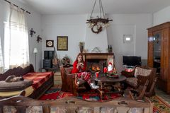Young woman on the eve of the New Year or Christmas. New Year or Christmas design. A young woman in pajamas and cat sits near a burning fireplace and a table stock image