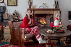 Young woman on the eve of the New Year or Christmas. New Year or Christmas design. A young woman in pajamas sits near a burning fireplace and a table with sweets stock photo