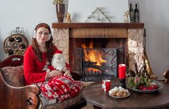 Young woman on the eve of the New Year or Christmas. New Year or Christmas design. A young woman in pajamas sits near a burning fireplace and a table with sweets royalty free stock photos