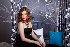Young woman in evening dress on the Christmas background Stock Photo