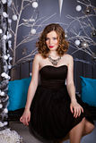 Young woman in evening dress sitting on the Christmas bench Royalty Free Stock Photography