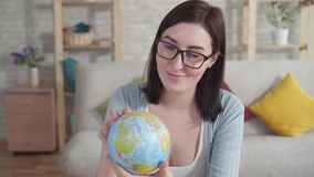 Young woman examines a globe holding. In her hands stock footage