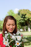 Young woman examining a bunch of flowers Royalty Free Stock Images