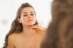 Young woman examining facial skin condition Stock Images