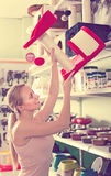 Young woman examining pretty cat houses. In pet shop stock photos