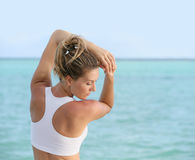 Young woman excercising by the sea. Portrait of fitness woman stretching out by the sea Stock Images