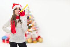 Young woman excited for Christmas with party blower Stock Images