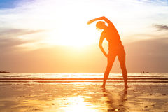 Young woman, exercise on the beach at sunset. Stock Photo