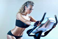 Young woman on exercise bicycle Stock Photo